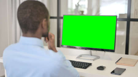 Businessman Looking at Desktop with Green Chroma Key Screen