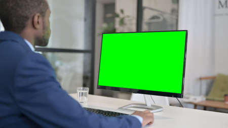 African Businessman Using Desktop with Green Chroma Key Screen