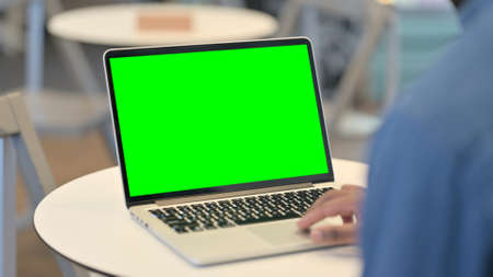 Man Working on Laptop with Green Chroma Key Screen, Rear View