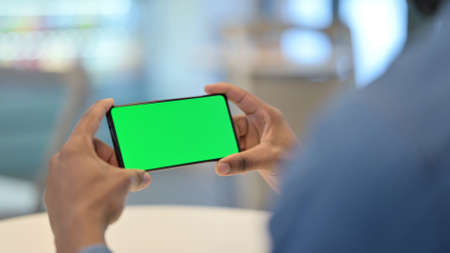 African Man Looking at Smartphone with Green Chroma Key Screen Zdjęcie Seryjne