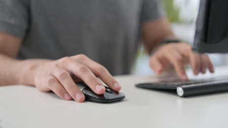 Hands of Young Man Using Mouse on Desktop, Close Up