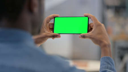 African Man Watching Video on Smartphone with Chroma Screen