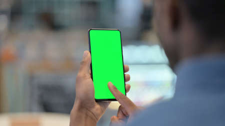 African Man Using Smartphone with Green Chroma Key Screen Standard-Bild