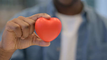 Close Up of African Man Holding Heart Shape Object Standard-Bild