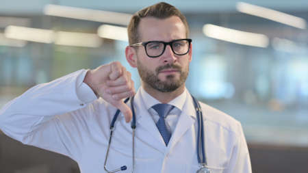 Portrait of Thumbs Down Gesture by Young Male Doctor