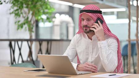 Arab Businessman with Laptop Talking on Smartphone