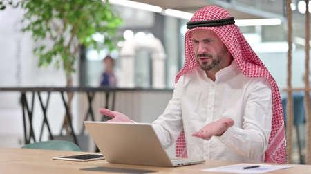 Loss, Arab Businessman reacting to Failure on Laptop