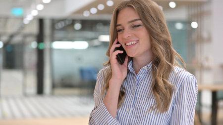 Portrait of Cheerful Businesswoman Talking on Phone