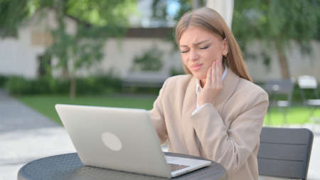 Businesswoman with Laptop having Toothache in Outdoor Cafe 스톡 콘텐츠