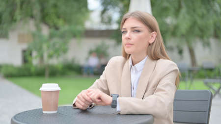 Businesswoman Waiting, Checking Time in Outdoor Cafe