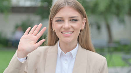 Outdoor Portrait of Businesswoman Waving at the Camera