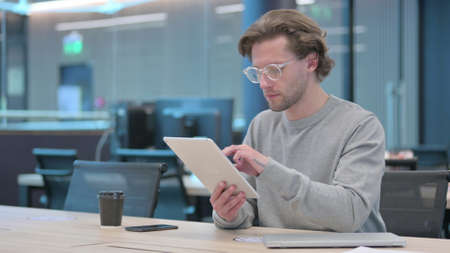 Young Man using Tablet in Office 스톡 콘텐츠