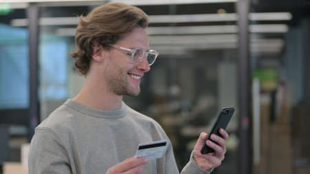 Portrait of Young Man Doing Online Shopping on Smartphone