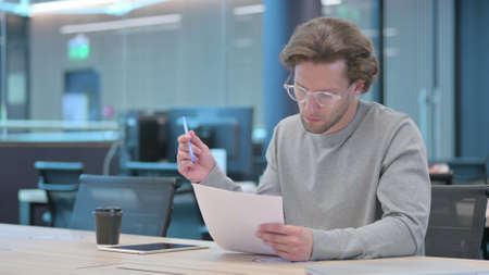 Young Man Reading Documents in Office