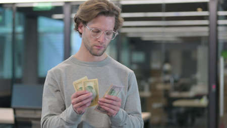 Portrait of Young Man Counting Dollars 스톡 콘텐츠