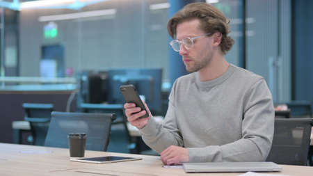 Young Man using Smartphone in Office