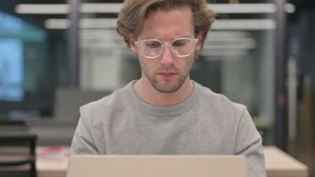 Portrait of Young Man Working on Laptop in Office 스톡 콘텐츠