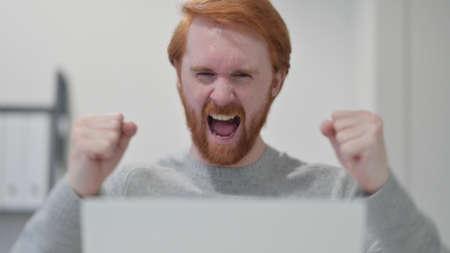 Beard Redhead Man Celebrating while using Laptop