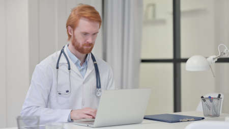 Redhead Male Doctor Working on Laptop