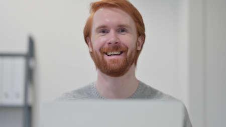 Beard Redhead Man with Laptop Smiling at Camera