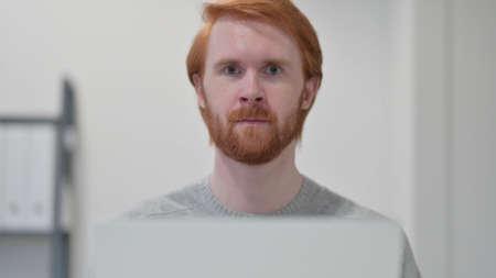 Beard Redhead Man with Laptop Looking at Camera