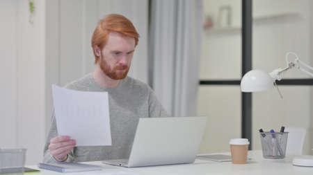 Beard Redhead Man Reading Paper While using Laptop at Work 스톡 콘텐츠