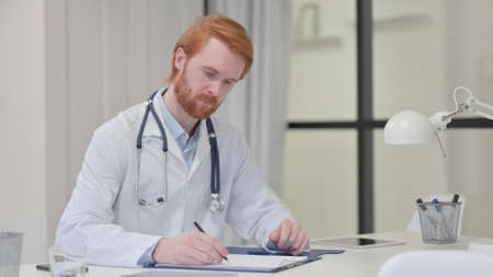 Redhead Male Doctor Writing on Paper at Work