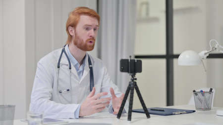 Redhead Male Doctor Recording Video on Camera 스톡 콘텐츠