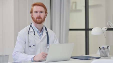 Redhead Male Doctor Looking at Camera