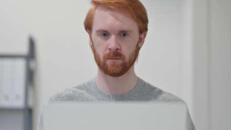 Young Beard Redhead Man using Laptop