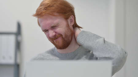 Beard Redhead Man with Laptop having Neck Pain 스톡 콘텐츠