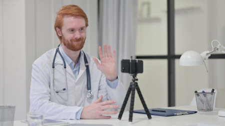 Redhead Male Doctor Doing Video chat on Smartphone
