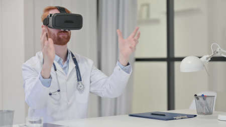 Young Redhead Male Doctor using VR Set 스톡 콘텐츠