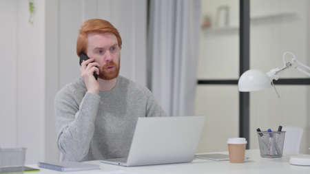 Beard Redhead Man with Laptop Talking on Smartphone