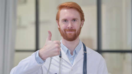 Thumbs Up Sign by Redhead Male Doctor
