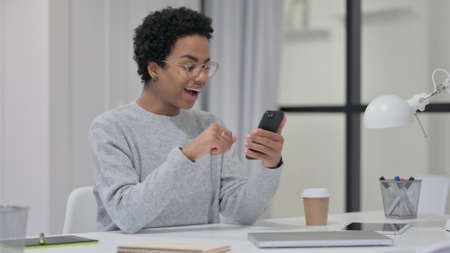 African Woman Celebrating Success while using Smartphone