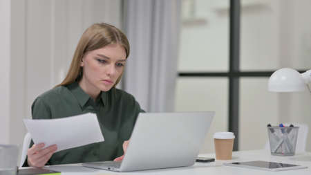 Young Woman Reading Documents while working on Laptop