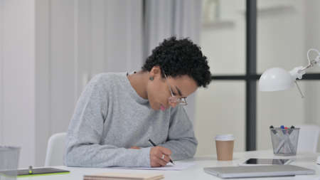 African Woman Writing on Paper at Work 스톡 콘텐츠