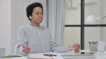 African Woman Meditating with Music on Smartphone