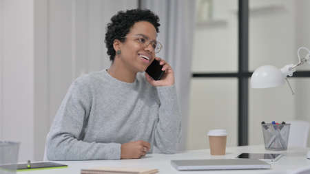 African Woman Talking on Smartphone at Work