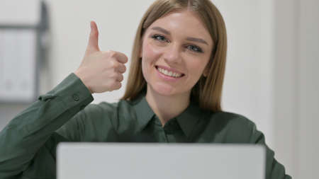 Thumbs up by Woman with Laptop