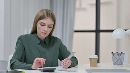 Young Woman using Calculator while Counting Dollars