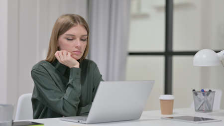 Young Woman with Laptop Taking Nap at Work