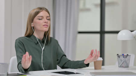 Young Woman Meditating with Music on Smartphone