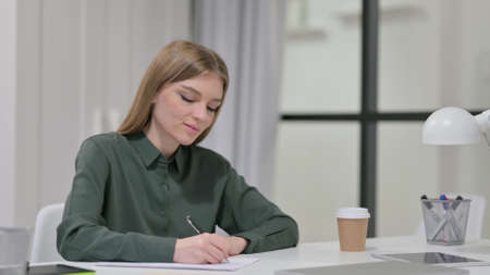 Pensive Young Woman Writing on Paper, Thinking