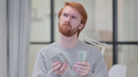 Young Beard Redhead Man Counting Dollars