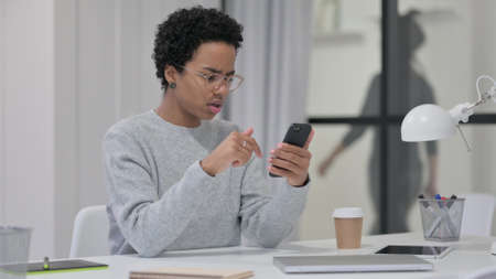 African Woman having Loss while using Smartphone