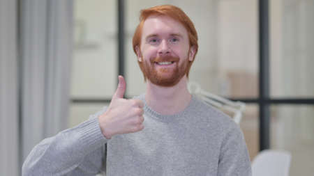 Young Beard Redhead Man showing Thumbs Up Sign