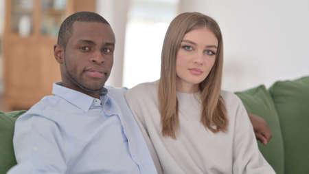 Interracial Couple Sitting and Looking at Camera