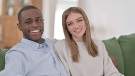 Interracial Couple Sitting on Sofa and Smiling at Camera 스톡 콘텐츠